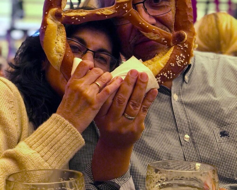 Oktoberfest couple holding brezel on face